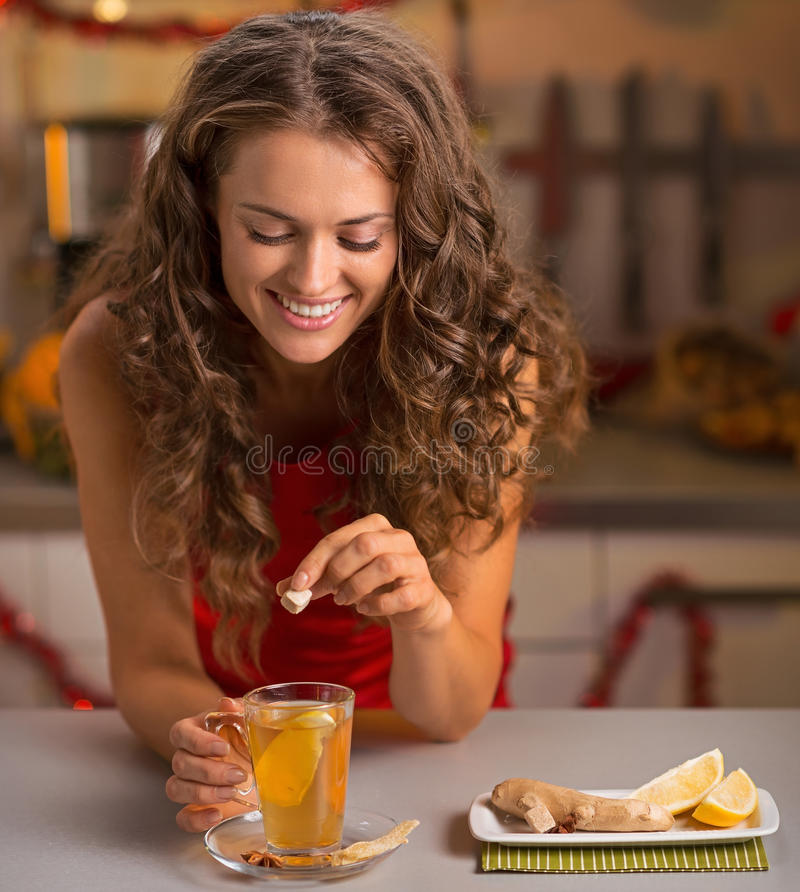 Happy young woman putting brown sugar cube into ginger tea. Happy young woman in red dress putting brown sugar cube into ginger tea stock photography