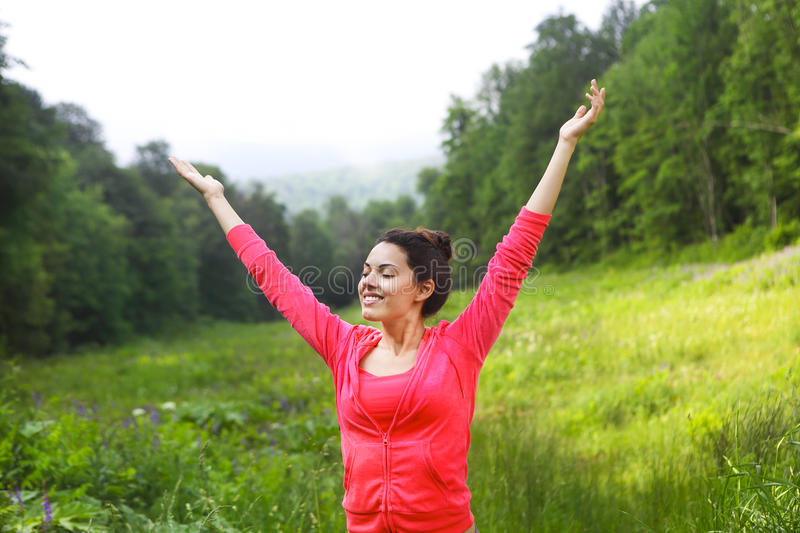 Happy young woman raised hands up at mountain forest royalty free stock photos
