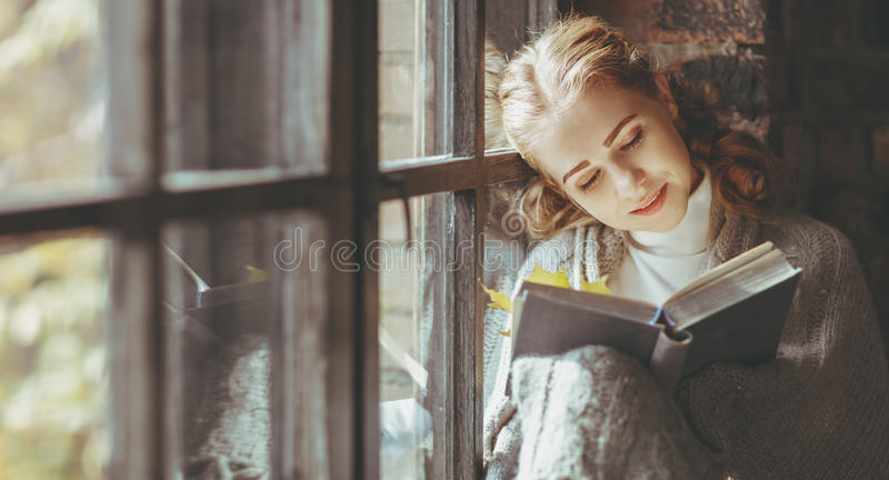 Happy young woman reading book by window in fall royalty free stock photography