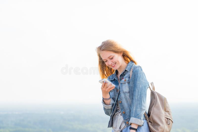 Happy young woman reading messages, watching something on the Internet via smartphone and smiling in nature. Horizontal portrait, copy space royalty free stock image
