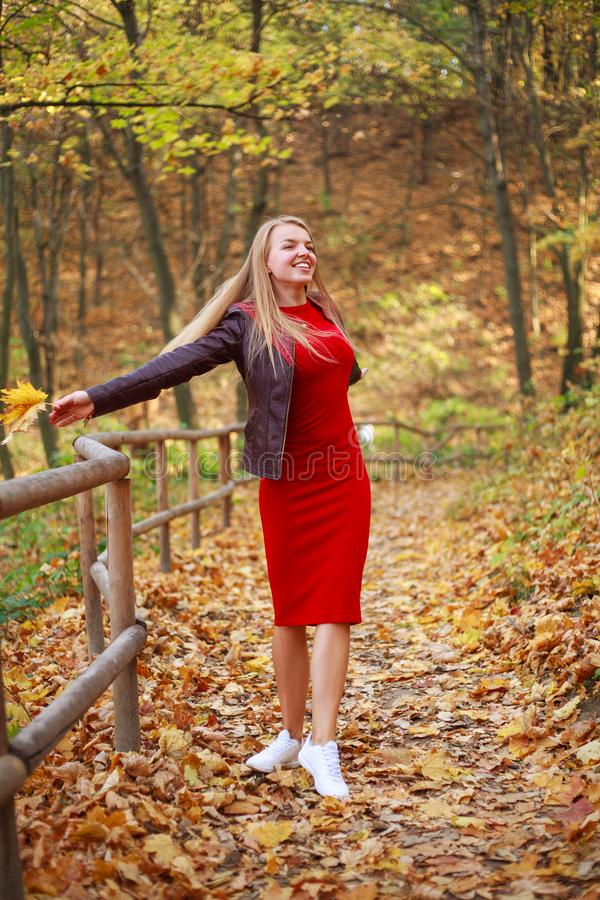 Happy young woman in red dress carelessly having fun in forest park enjoying natur stock images