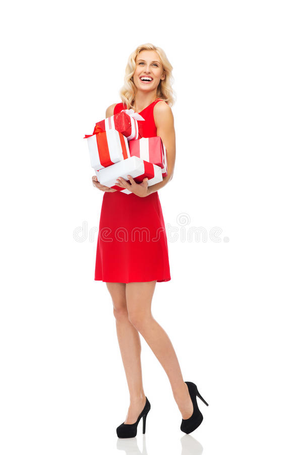 Happy young woman in red dress holding gift boxes royalty free stock images