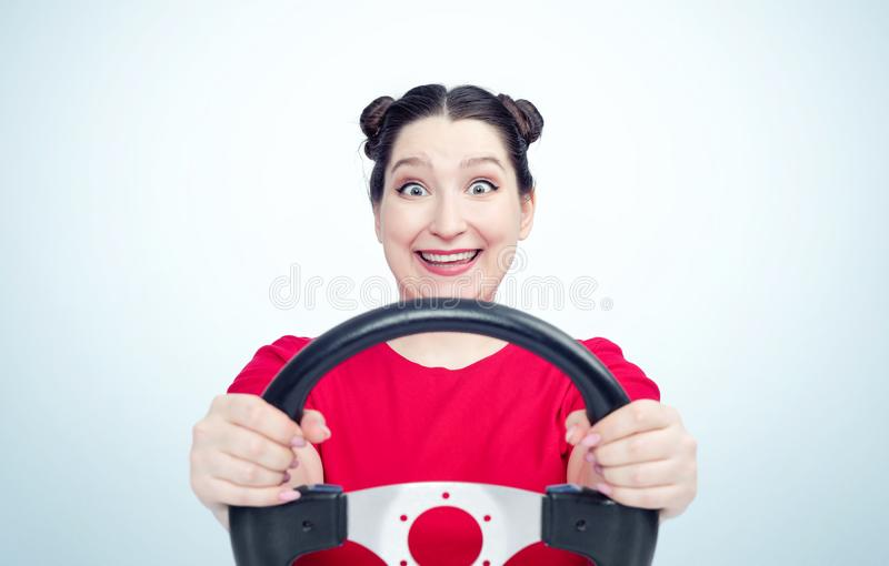 Happy young woman in red t-shirt with steering wheel on light blue background, car driver concept royalty free stock photography