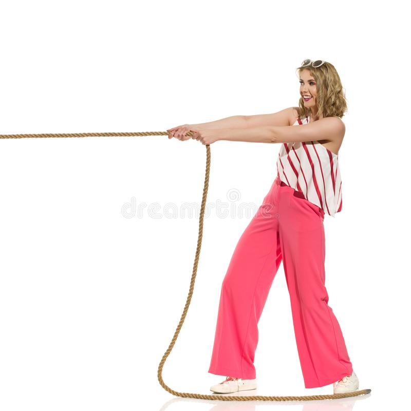 Happy Young Woman In Red Wide Leg Trousers Is Pulling The Rope. Looking away and smiling. Full length studio shot isolated on white stock images