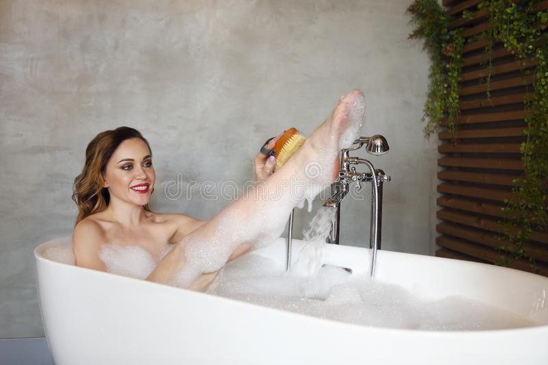 Happy young woman relaxing in bathtub stock images