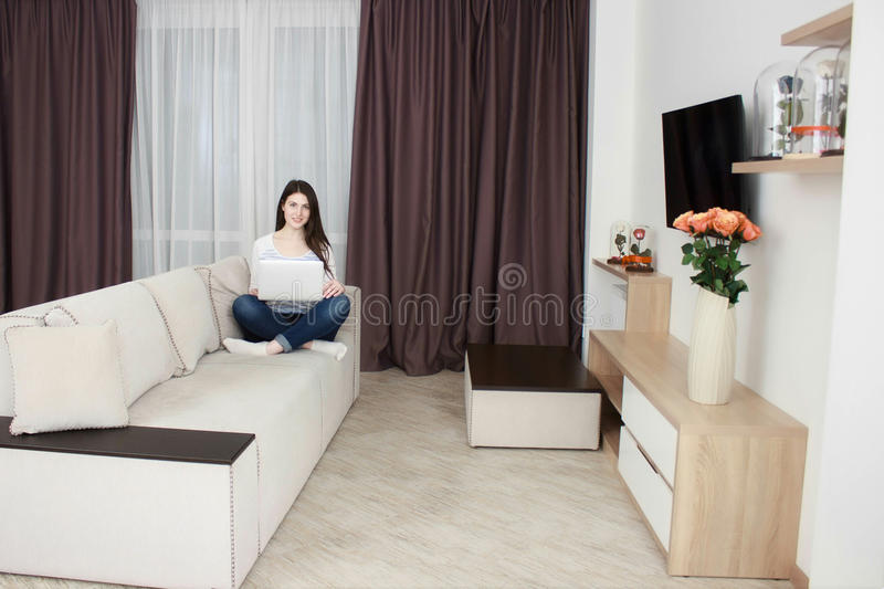 Happy young woman is relaxing on comfortable couch and using laptop at home stock photos