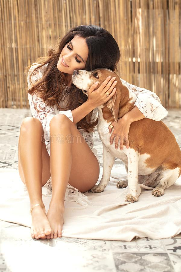 Happy young woman playing with dog stock photography