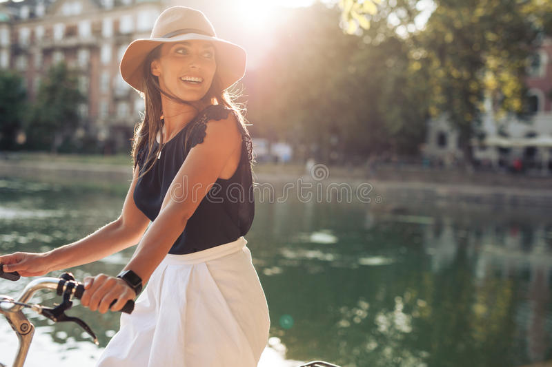 Happy young woman riding bicycle by a pond. Portrait of happy young woman riding bicycle by a pond. Woman wearing a hat on a summer day looking over her shoulder royalty free stock photography
