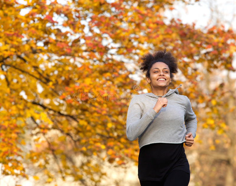 Happy young woman running outdoors in the park stock images