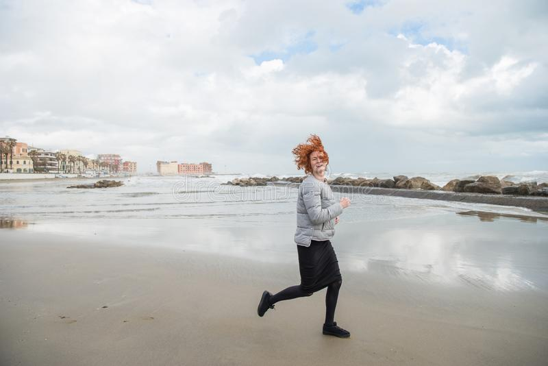 happy young woman running by seashore on cloudy day royalty free stock images