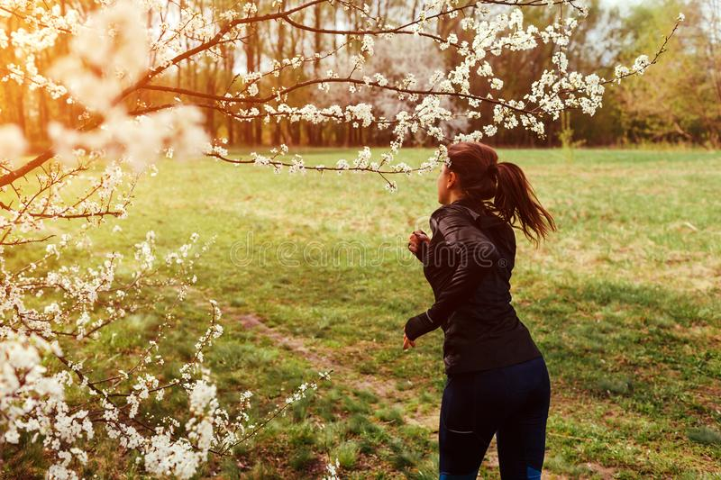 Happy woman running in spring forest. Helathy lifestyle. Happy young woman running in spring forest among blooming trees in the morning. Helathy lifestyle royalty free stock photos
