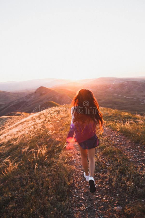Happy young woman running in sunset light. Freedom concept. Happy young woman running on feather grass field in sunset light. Nature lifestyle and amazing view royalty free stock photography