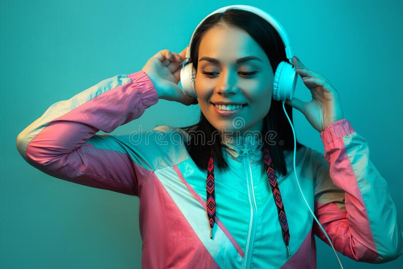Happy young woman in 90s style sport outfit with white headphones listening to music in neon lights at studio. Happy young woman in 90s style sport outfit with royalty free stock photography