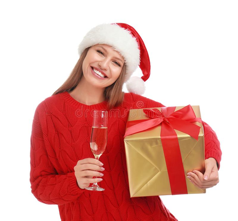 Happy young woman in Santa hat with Christmas gift and glass of champagne stock photos
