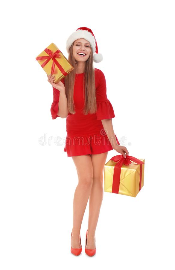 Happy young woman in Santa hat with Christmas gifts on white royalty free stock photo