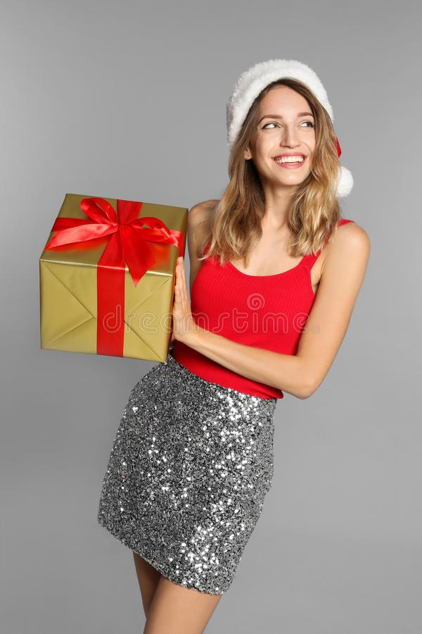Happy young woman in Santa hat with gift box on grey background. Christmas celebration royalty free stock photography