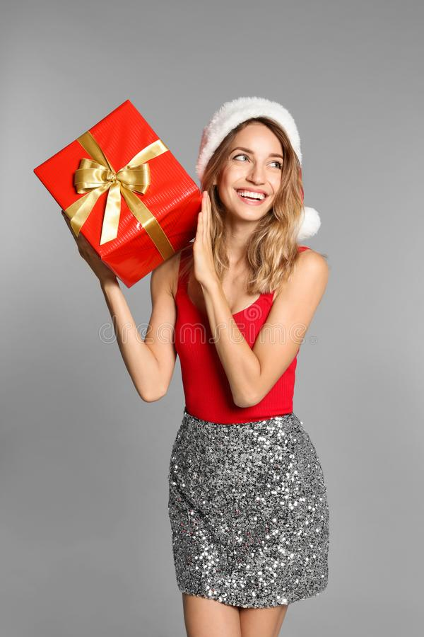 Happy young woman in Santa hat with gift box on grey background. Christmas celebration royalty free stock images