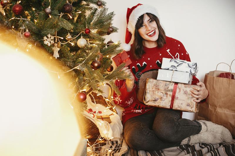 happy young woman in santa hat holding pile of gift boxes at golden beautiful christmas tree with lights in festive room. happy w stock photo