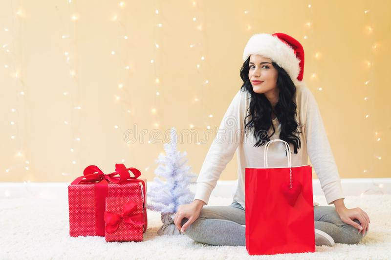 Happy young woman with santa hat holding a shopping bag. On a shiny light background stock photos
