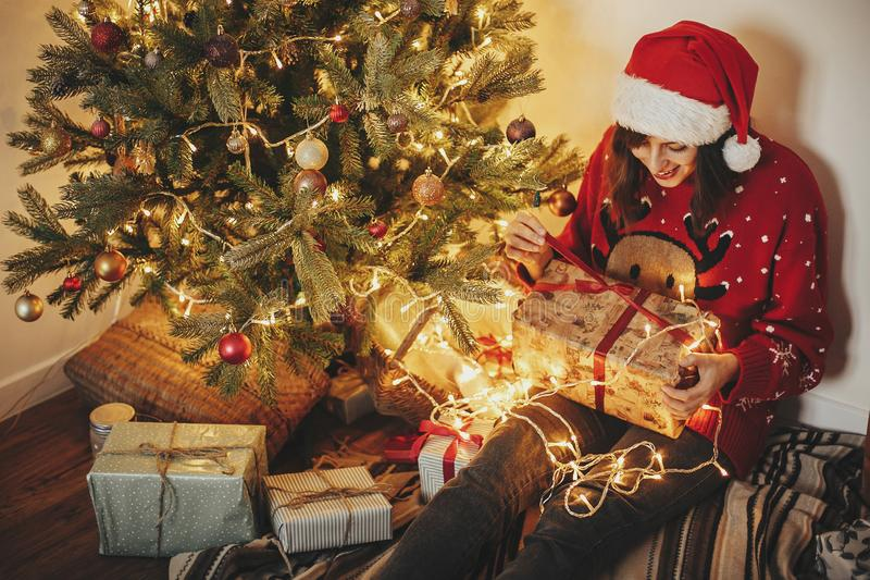 happy young woman in santa hat opening gift box at golden beautiful christmas tree with lights and presents in festive room. stock photos