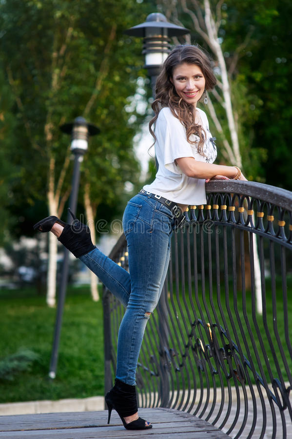 Happy young woman in shirt and jeans standing on the bridge.  royalty free stock image