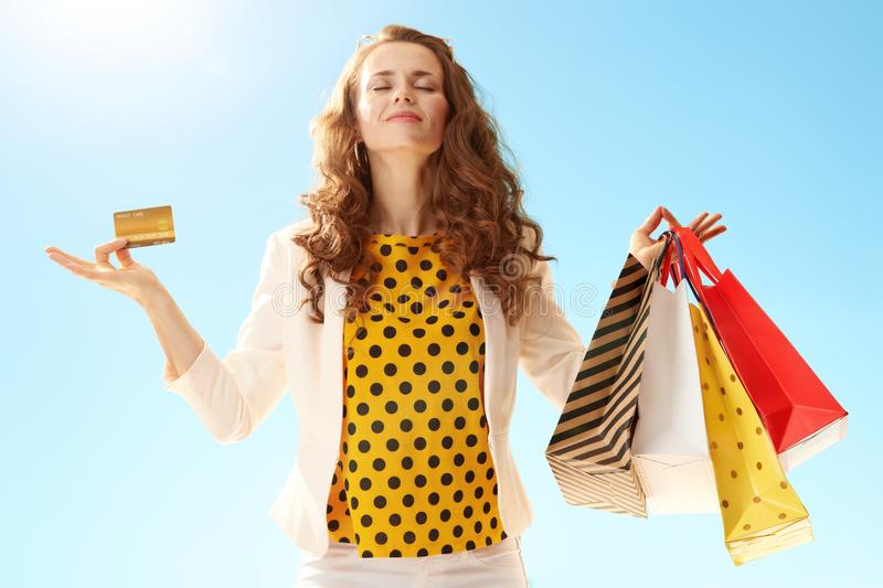 Happy young woman with shopping bags and credit card doing yoga. Happy young woman in a light jacket with shopping bags and credit card doing yoga against blue stock image