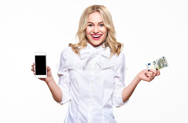 Happy young woman showing mobile phone blank screen and holding a five Euro banknote, smiling with excitement. royalty free stock photo