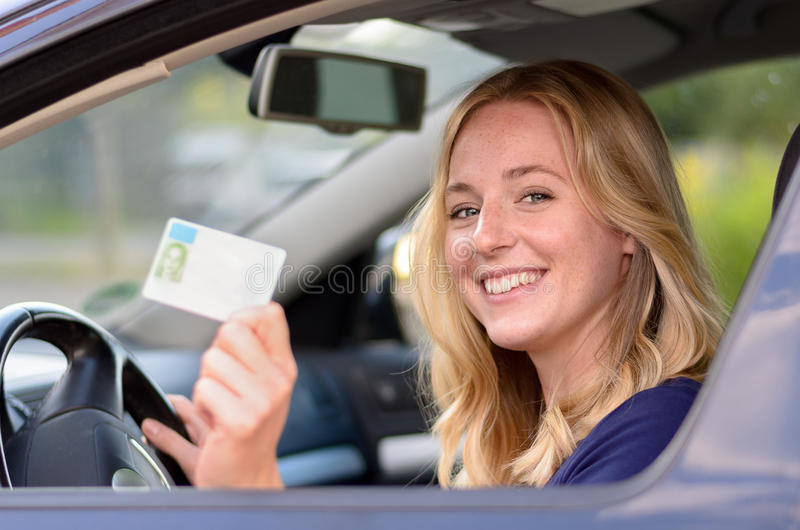 Happy young woman showing off her drivers license stock photography