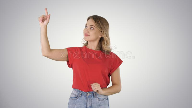 Happy young woman showing a product pointing with her finger to sides Presentation on gradient background. royalty free stock photos