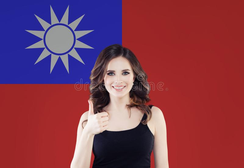 Happy young woman showing thumb up on the Taiwan flag background, travel, volunteer work and learn chinese language concept stock photography