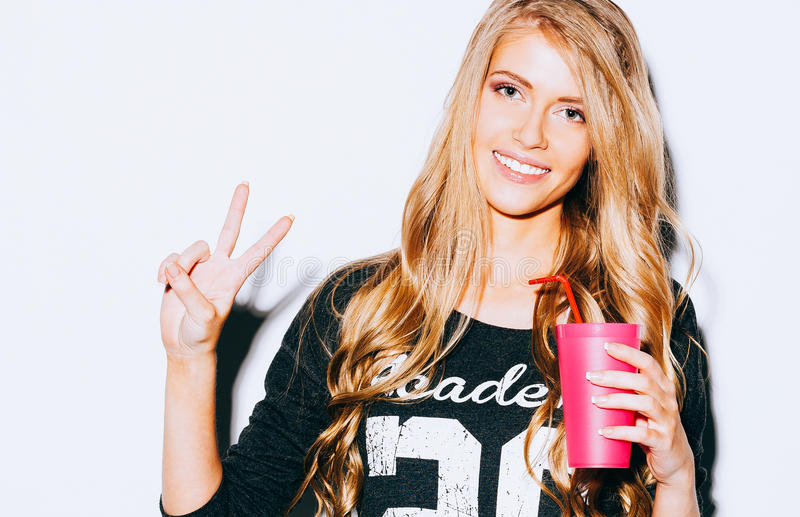 Happy Young Woman Showing Victory Sign and holding a pink glass with straw in hand On White Background. Close up. Indoor. Warm col royalty free stock photography