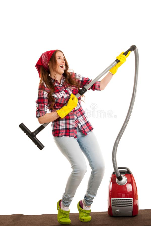Happy young woman singing as she is cleaning with vacuum cleaner royalty free stock image