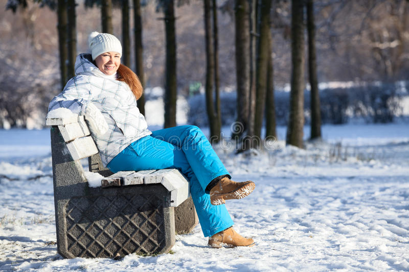 Happy young woman sitting on bench in winter. Outdoors, copyspace royalty free stock photography