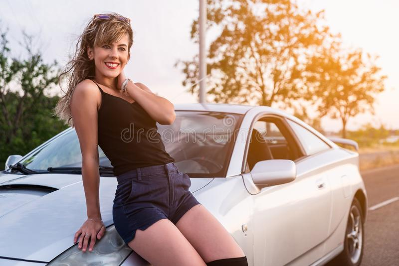 Happy young woman sitting on bonnet of car stock photography