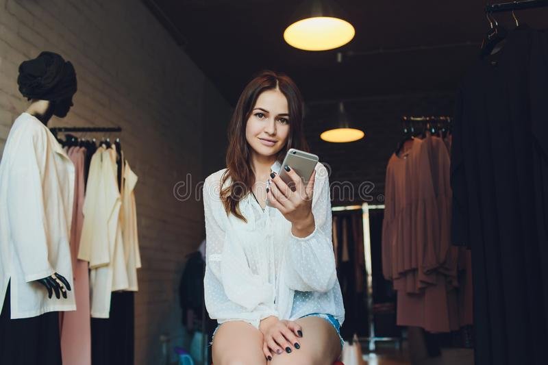Happy young woman sitting at the clothing store with shopping bags and talking on mobile phone. stock image