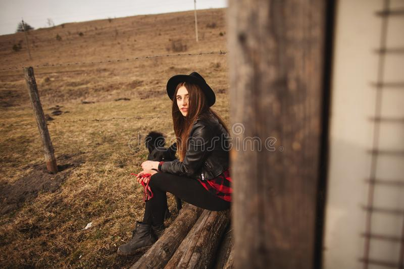 Happy young woman sitting with her black dog in fron of old wooden house royalty free stock images