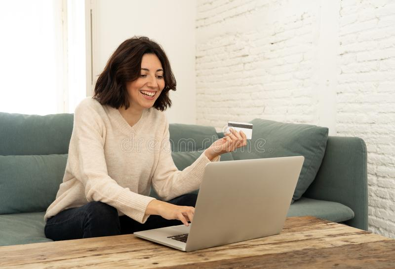 Happy young woman sitting with laptop and a credit card shopping online at home royalty free stock images