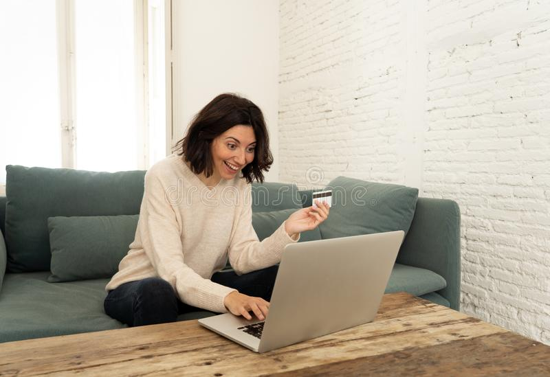 Happy young woman sitting with laptop and a credit card shopping online at home stock image