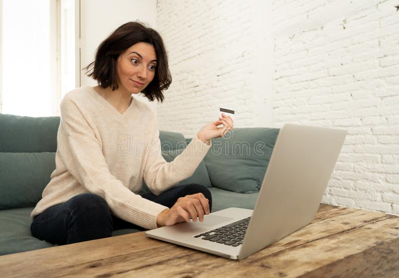 Happy young woman sitting with laptop and a credit card shopping online at home stock images