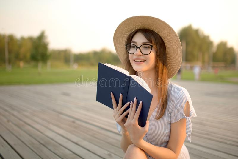 Happy young woman sitting in the park. Smiling and holding a book in his hands royalty free stock image
