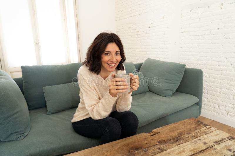 Happy young woman sitting on sofa at home with a hot beverage. In leisure and spare time concept royalty free stock photos