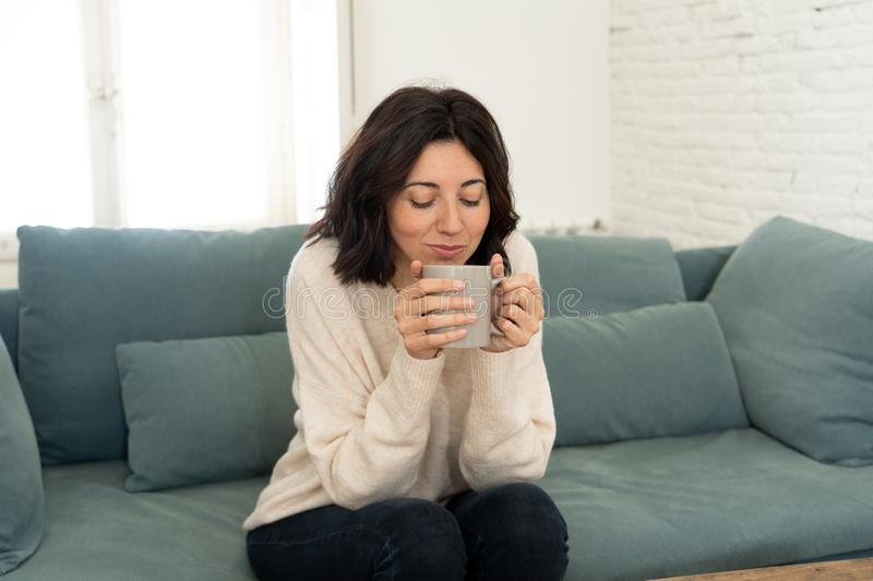 Happy young woman sitting on sofa at home with a hot beverage. In leisure and spare time concept stock image