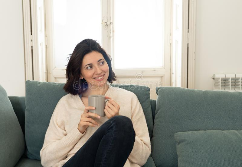 Happy young woman sitting on sofa at home with a hot beverage. In leisure and spare time concept stock photography