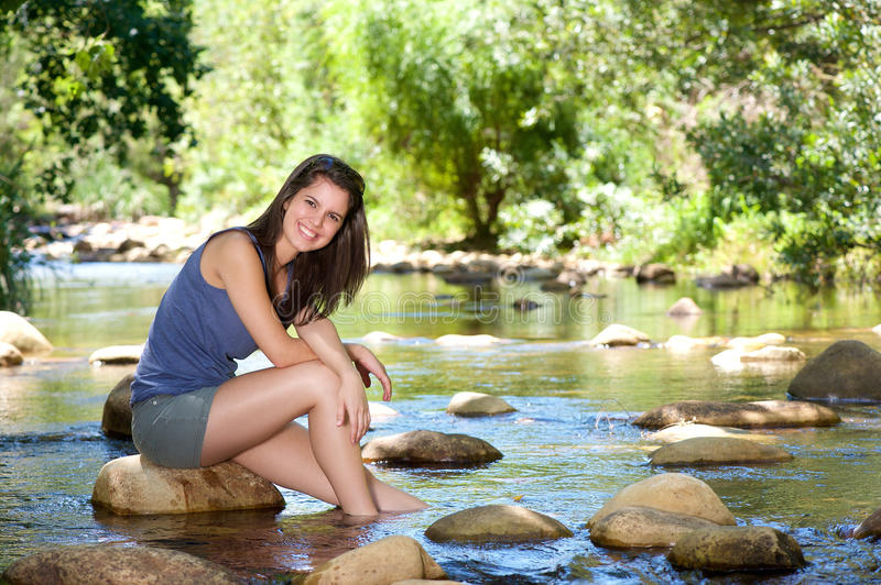 Happy young woman sitting by stream with feet in water royalty free stock photography