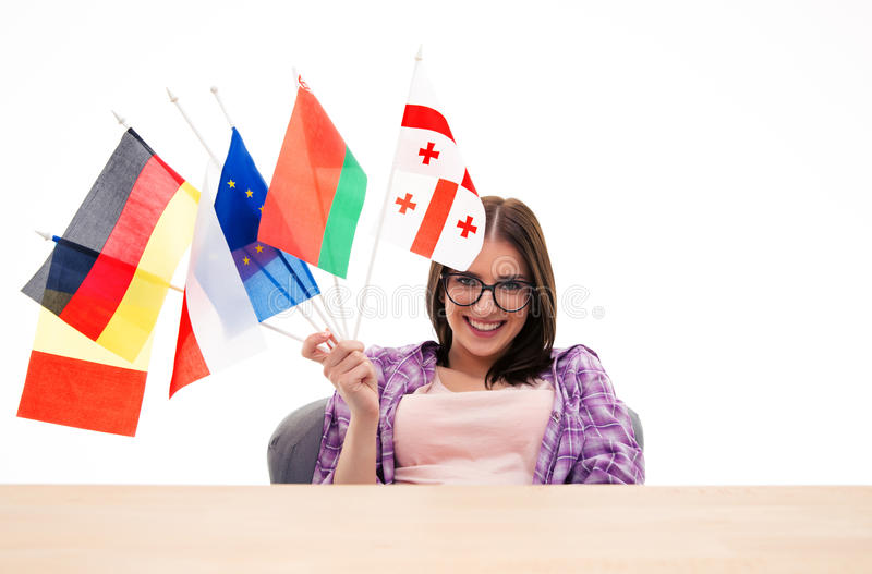 Happy young woman sitting at the table with international flags royalty free stock photography