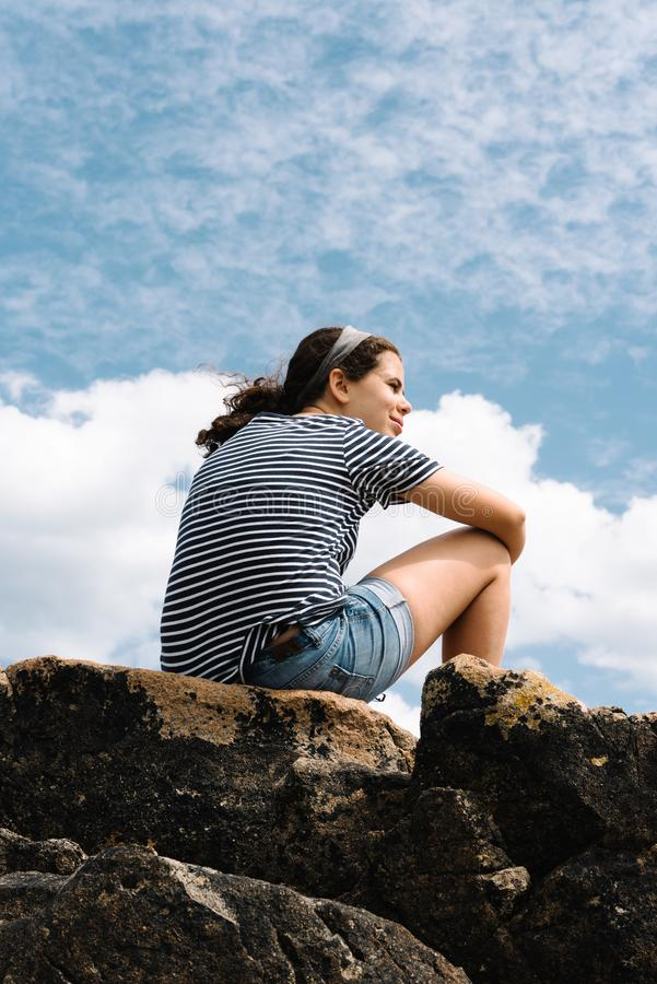 Happy young woman on top of rocks against sky stock photos