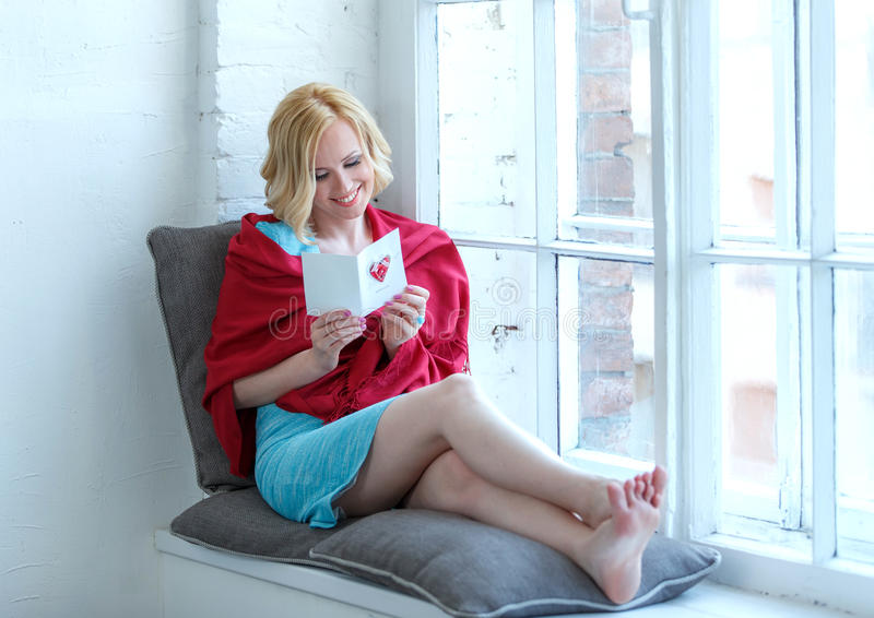 Happy young woman sitting on windowsill with love postcard royalty free stock images