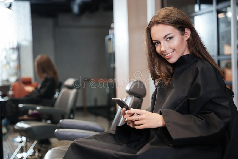 Happy young woman with smartphone at hair salon royalty free stock photos