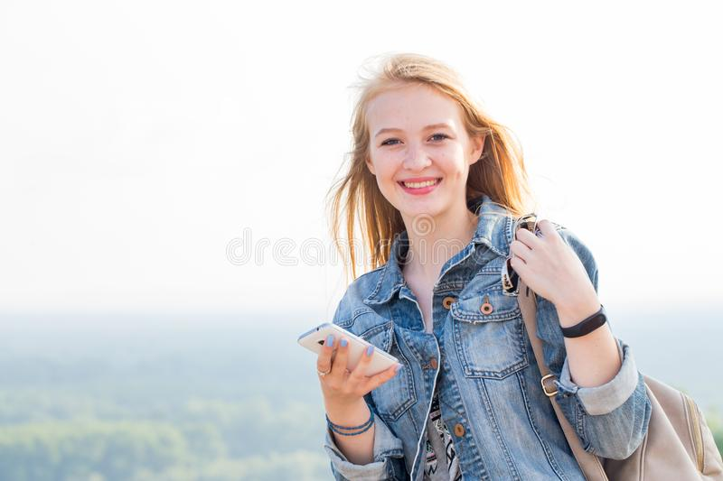 Happy young woman with smartphone on hand with smile looking at camera. Travel, Internet, modern technologies, phone, lifestyle. Concepts royalty free stock images