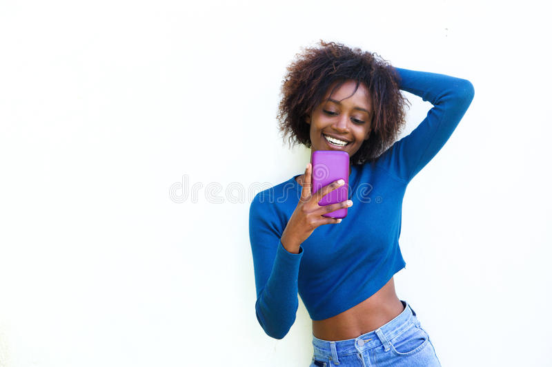 Happy young woman smiling with cell phone against white background. Portrait of a happy young woman smiling with cell phone against white background stock photography